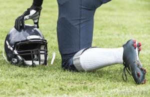 football-player-kneeling-with-helmet-off